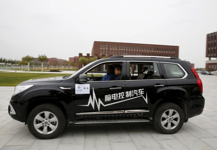 Researcher Zhang Zhao wearing a brain signal-reading equipment moves a car forward with his brain wave during a demonstration at Nankai University in Tianjin