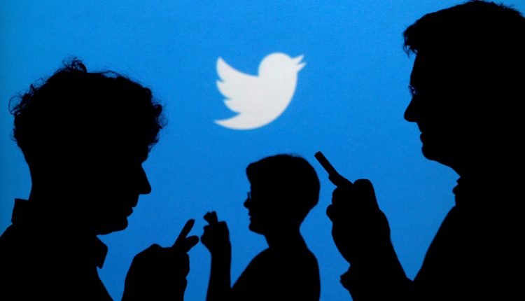 Image: People holding mobile phones are silhouetted against a backdrop projected with the Twitter logo